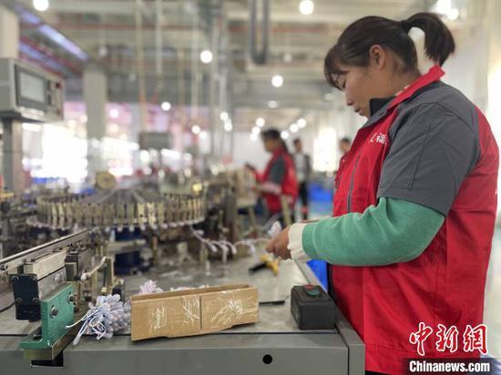 图为东川当地一家生产电子元件的工厂内,工人正在工作。 缪超 摄