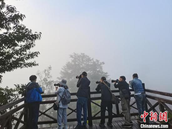 图为摄影家正在进行拍摄。 中国民俗摄影协会供图
