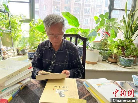 作家吴然向记者介绍创作经历。 刘丽慧 摄