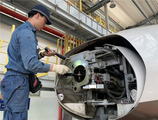 昆明动车所检修库,工作人员正在对列车进行检修。(新华网 念新洪/摄)