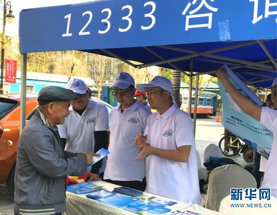 工作人员向市民宣传和推广12333。新华网 詹晶晶 摄