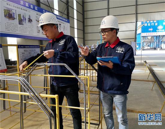 中铁二十一局集团路桥公司技术人员测量钢件。