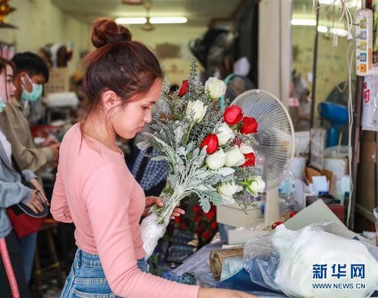 2月14日,在泰国曼谷帕空鲜花市场的一家花店,工作人员将从云南进口的鲜花制作成花束和花盒。 新华社记者 张可任 摄