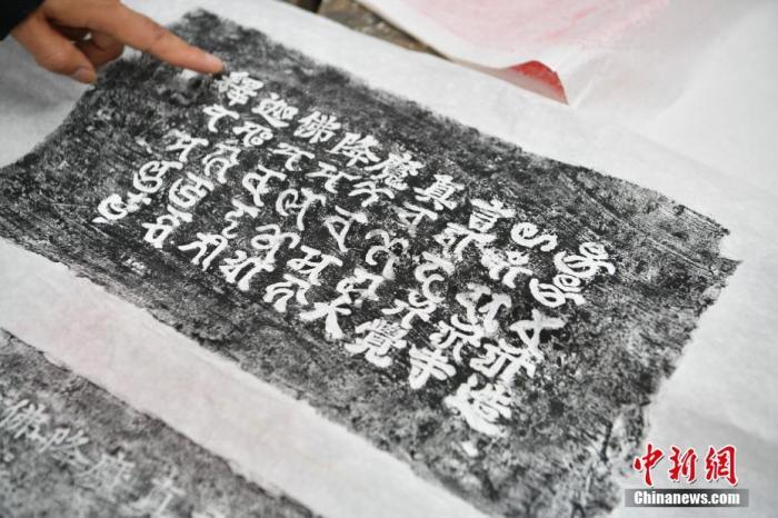 5月27日,尹恒展示塔砖拓片。中新社记者 刘冉阳 摄