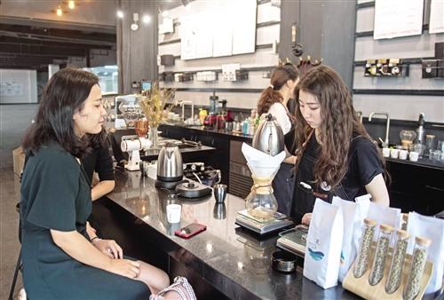 云南普洱大力发展咖啡产业。在云南省普洱市艾哲咖啡店,顾客在购买咖啡饮品(5月9日摄)。 新华社记者 胡 超摄