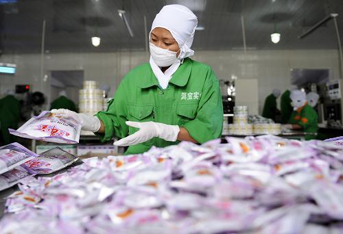 工作人员在云南省大理白族自治州洱源县洱宝话梅厂内包装酸角糕和青梅糕。新华社记者 戴旭明 摄