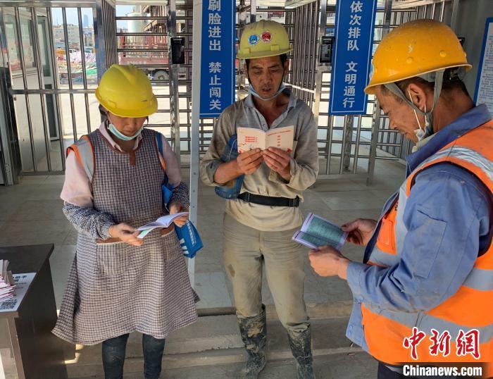 图为农民工阅读《保障农民工工资支付条例》宣传册。 孙洋洋 摄