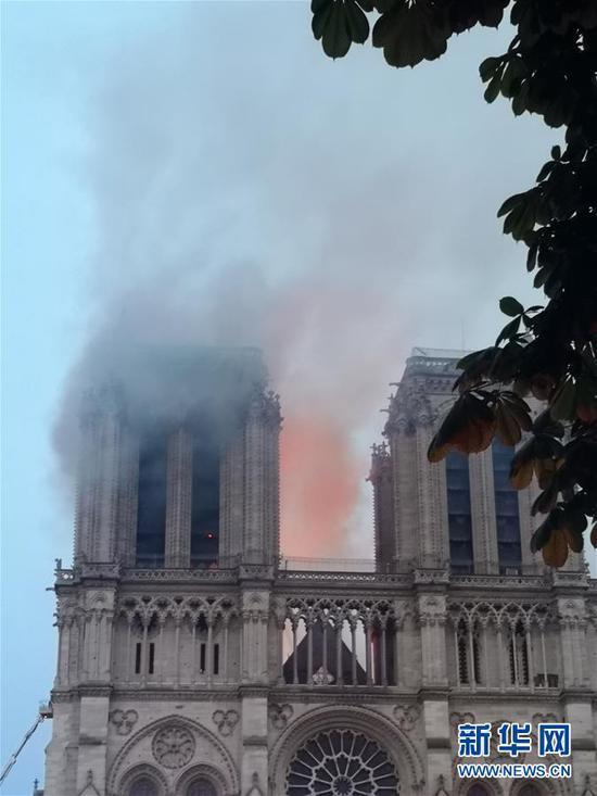 4月15日,在法国首都巴黎,发生大火的巴黎圣母院冒出浓烟。 新华社记者 杨一苗 摄