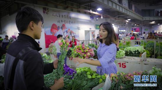昆明斗南鲜花交易市场,顾客正在挑选鲜花。新华网 潘越 摄