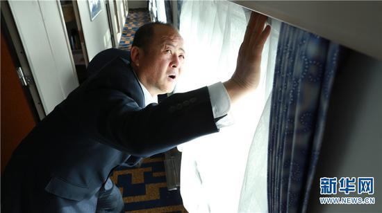 目前孙昆育在昆明客运段列车整备车间工作,车厢内所有的细节他都要关注到,图为孙昆育正在检查列车窗帘 新华网 潘越 摄