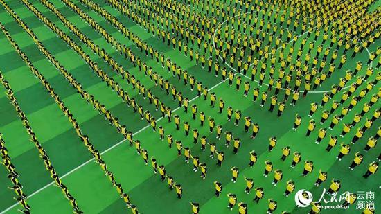 8月29日,云南省红河哈尼族彝族自治州蒙自市山师华清中学举行军训汇报演出暨开学典礼。图为学生们在表演手语操《感恩的心》。摄影:胡艳辉