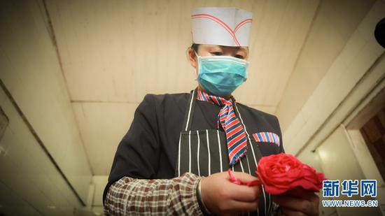 主厨苏琴仙在选花。(摄于4月28日)(新华网 潘越 摄)