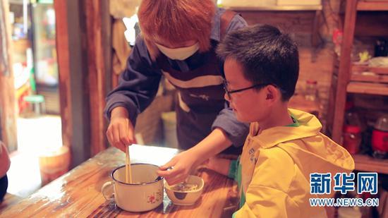 5月28日,段春萍和儿子。新华网 刘云 摄