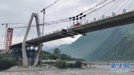 8月29日,工人在云南保泸高速公路勐古怒江特大桥进行吊装作业。