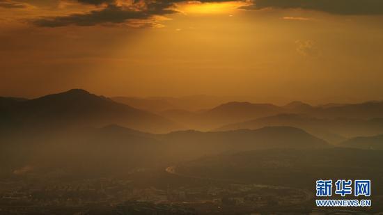9月3日,夕阳下的群山与山脚下的高速公路。(新华网 刘东 摄)