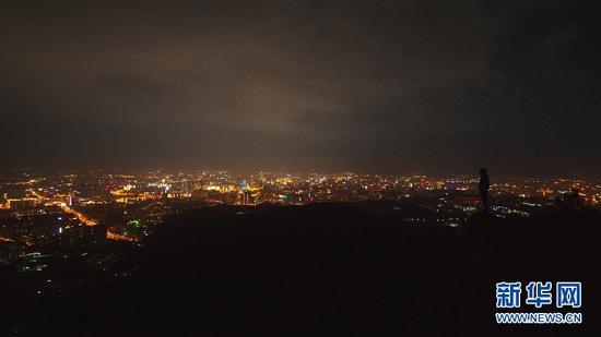 9月3日,站在长虫山顶岩石上观看城市夜景的游客。(新华网 刘东 摄)