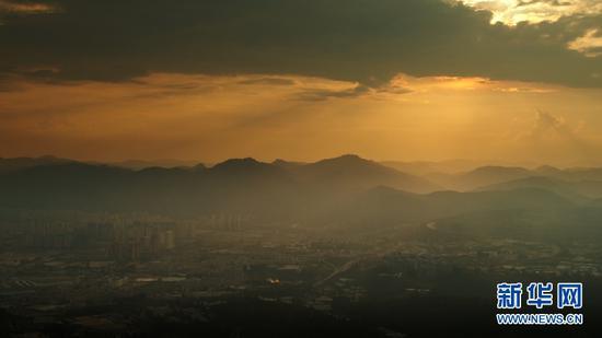9月3日,夕阳下的城市一角与群山。(新华网 刘东 摄)