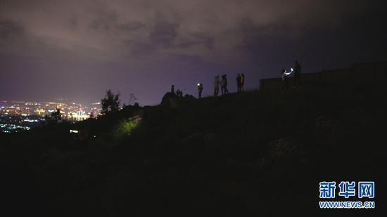 9月3日,深夜依旧在山顶打卡拍照的游客。(新华网 刘东 摄)