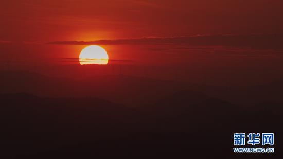 9月3日,已落入群山一角的太阳。(新华网 刘东 摄)