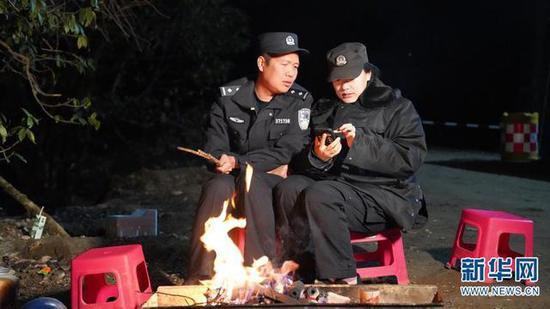 结束一天的巡逻,夫妻二人在警务室外的篝火旁与远方的孩子视频通话。