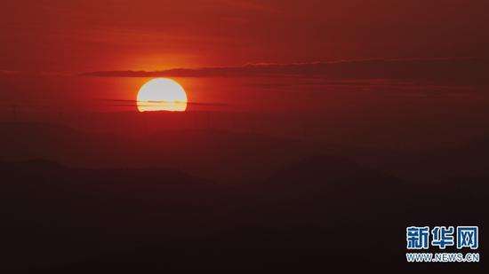 已落入群山一角的太阳。(新华网 刘东 摄)
