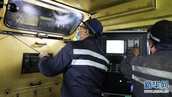 桂伟雄工友在镟轮机前进行镟轮作业(摄于2月1日)。新华网发(供图)