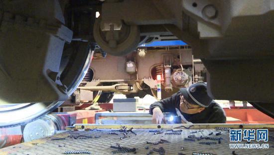 桂伟雄仔细检查镟修后的机车轮对踏面状态(摄于2月1日)。新华网发(供图)