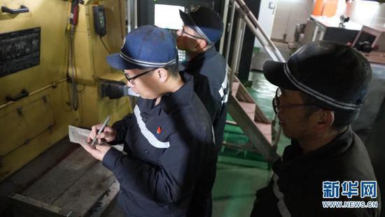 遇到机车车轮剥离的情况,桂伟雄和工友们一起研究解决办法(摄于2月1日)。新华网发(供图)