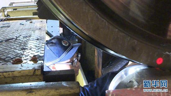 """桂伟雄钻入地下近3米深的镟轮坑开启一天的""""修脚""""业务。(摄于2月1日)新华网发(供图)"""