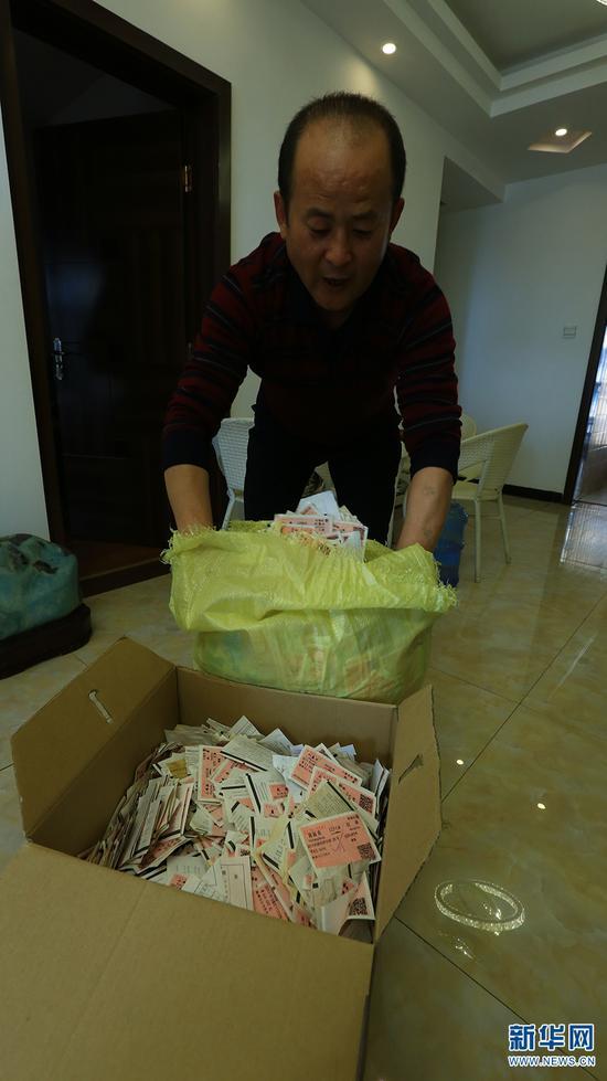 """一个纸盒、一个编织袋所装的火车票,有50多公斤重,这些都是孙昆育口中的""""宝贝""""。 新华网 潘越 摄"""