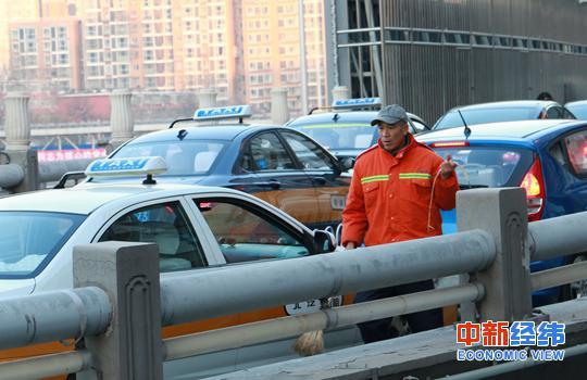 资料图:车流中的清洁工。 中新经纬摄