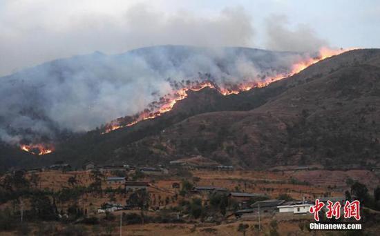 资料图:4月1日,四川西昌,响水沟森林大火逼近一村庄。中新社记者 刘忠俊 摄