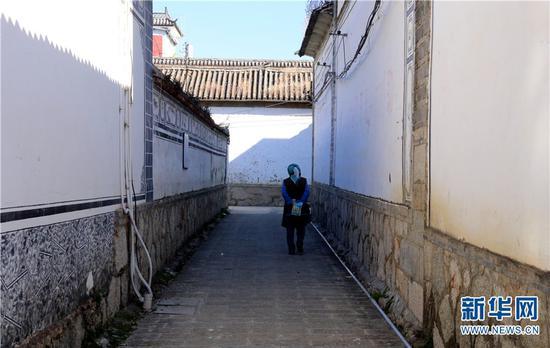 图为一位村民走在古生村巷道内。