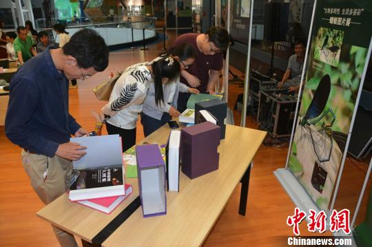 图为市民翻阅《中国蜻蜓大图鉴》。 中科院昆明动物研究所供图 摄