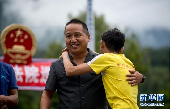 调解成功后,当事人与贡山县人民法院法官邓兴拥抱(8月30日摄)。新华社记者 江文耀 摄