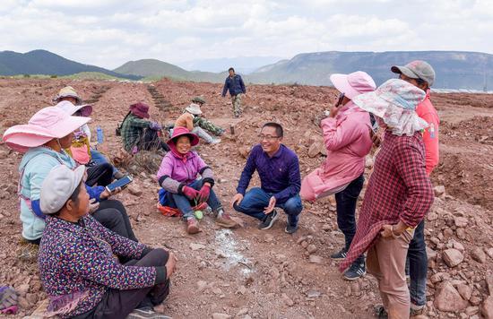 省扶贫办驻玉龙村第一书记、工作队长陆世军在了解贫困群众在乌嘴坪片区务工情况。