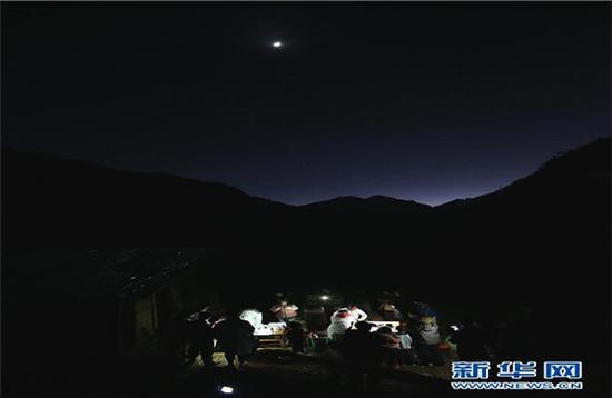 在云南怒江贡山县丙中洛镇碧汪村,来自贡山县丙中洛镇卫生院的医务人员借着手电筒的灯光为村民夜诊(1月12日摄)。