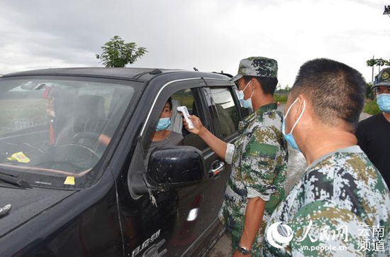 姐相乡边境封控点执勤人员正在为过往车辆驾乘人员测体温。(张帅摄)