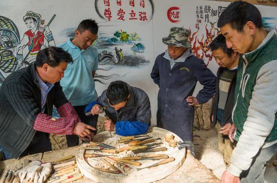 致富带头人杨元松正在教授残疾人学徒学习木雕(苏金泉 摄)