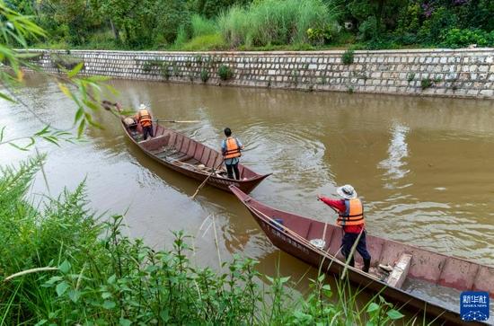 9月4日,环卫工人撑船在海洪湿地公园河道内工作。