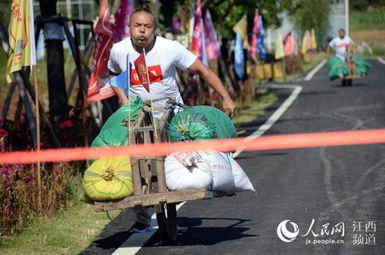 江西:独轮车推稻谷比赛中,一名农民选手冲向终点线。