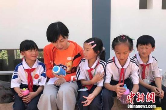 VIPKID联合创始人陈媛与乡村小学的孩子们在一起