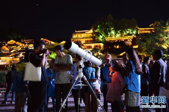9月24日,游客和市民在云南省丽江市玉河广场观测月亮。