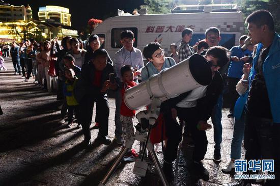 9月24日,游客和市民在云南省丽江市玉河广场排队观测月亮。