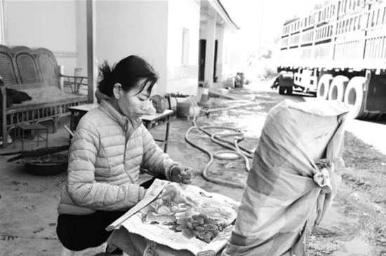 祥临公路旁的小小加水站里,丈夫忙着洗车加水,罗芹美蹲在旁边绣十字绣。