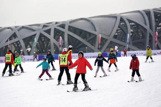 """小朋友在教练的带领下在""""鸟巢""""附场滑雪场滑雪。鞠焕宗摄"""