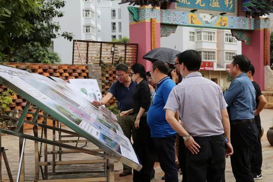 ▲华宁县政府工作人员详细介绍碗窑村产业规划情况