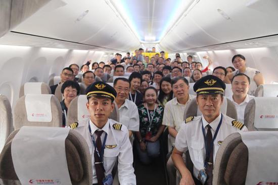 当上飞行员的和超(前排左一)将上海老志愿者们带回云南,众人在机舱内合影。