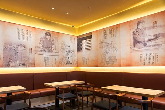 茶铺内的墙上绘有龙润大师制茶图