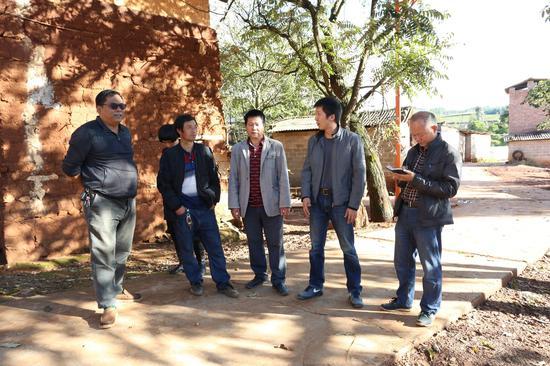 利民乡党委书记王敏(右二)向干塘子村民小组副组长候文海了解情况